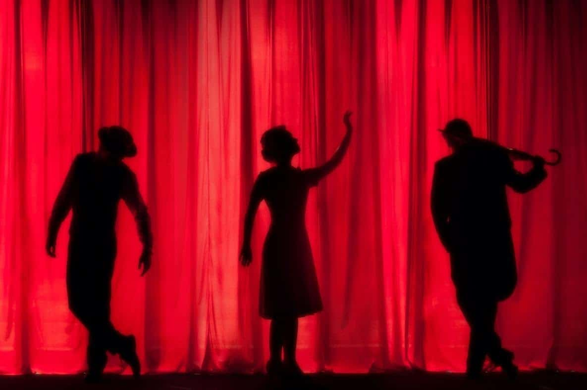 silhouette of musicians and dancers behind a red curtain