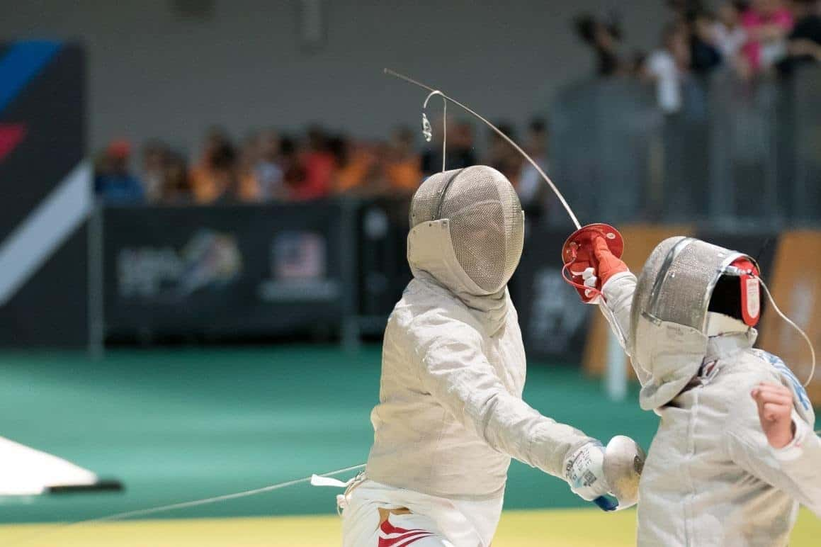 two people fencing during contest, crossing swords