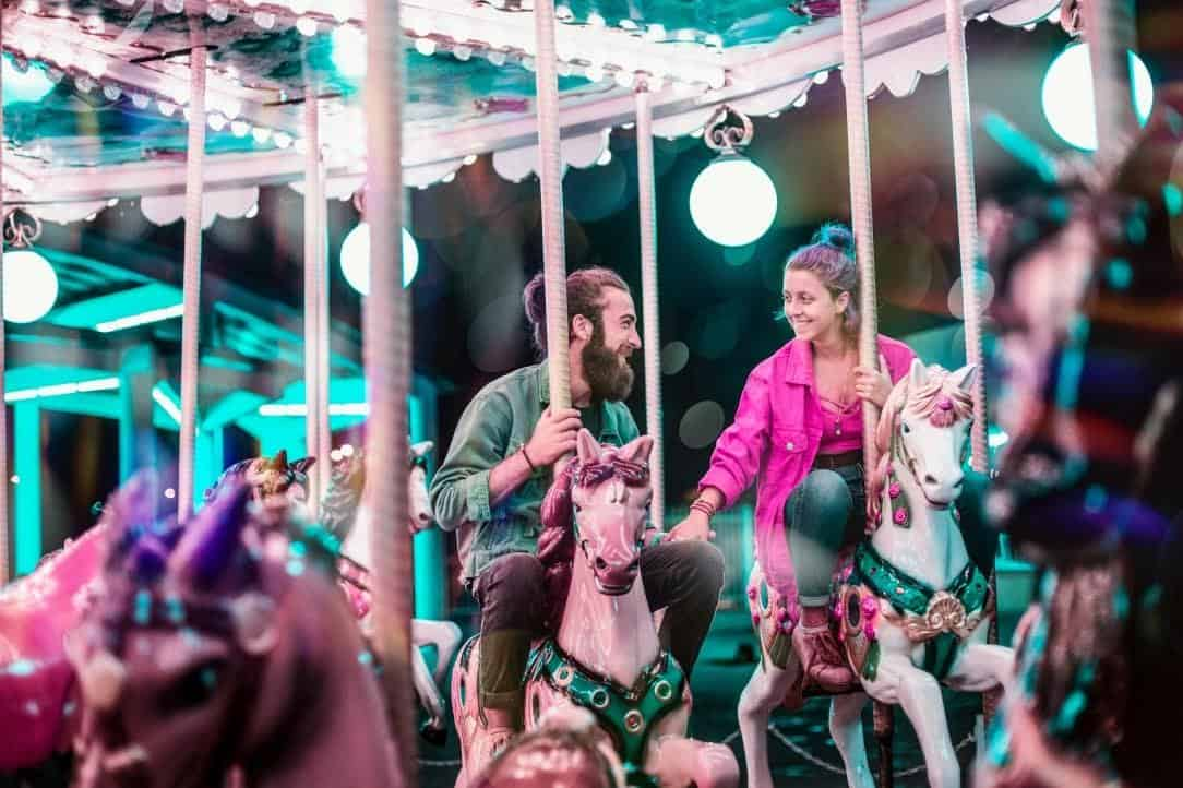 couple smiling on a horse marry-go-round at a carnaval