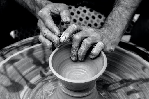 person making clay pottery on pottery wheel