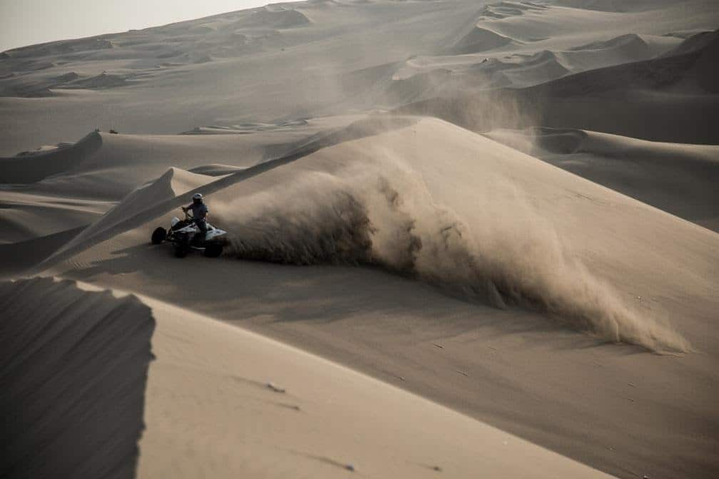 quadbike driving over a sand dune with a cloud of dust behind him