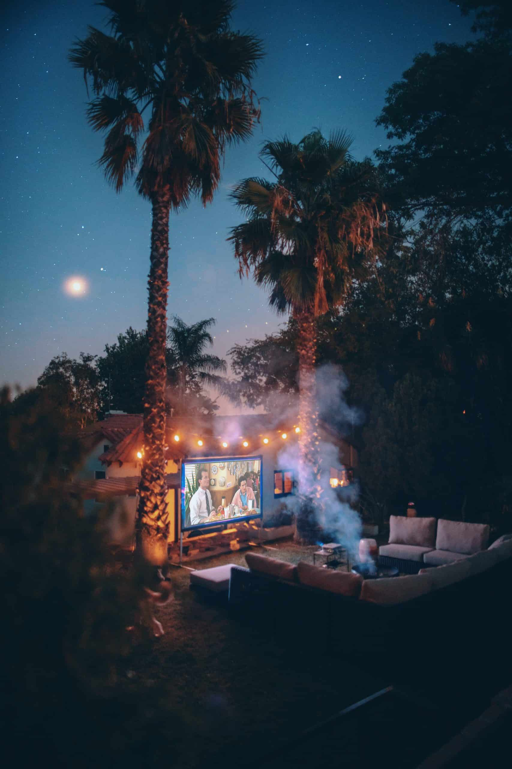 back yard hangout sofa circle with a screen projector and a movie