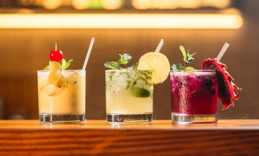 3 beautiful cocktails with straws and herbs on a bar