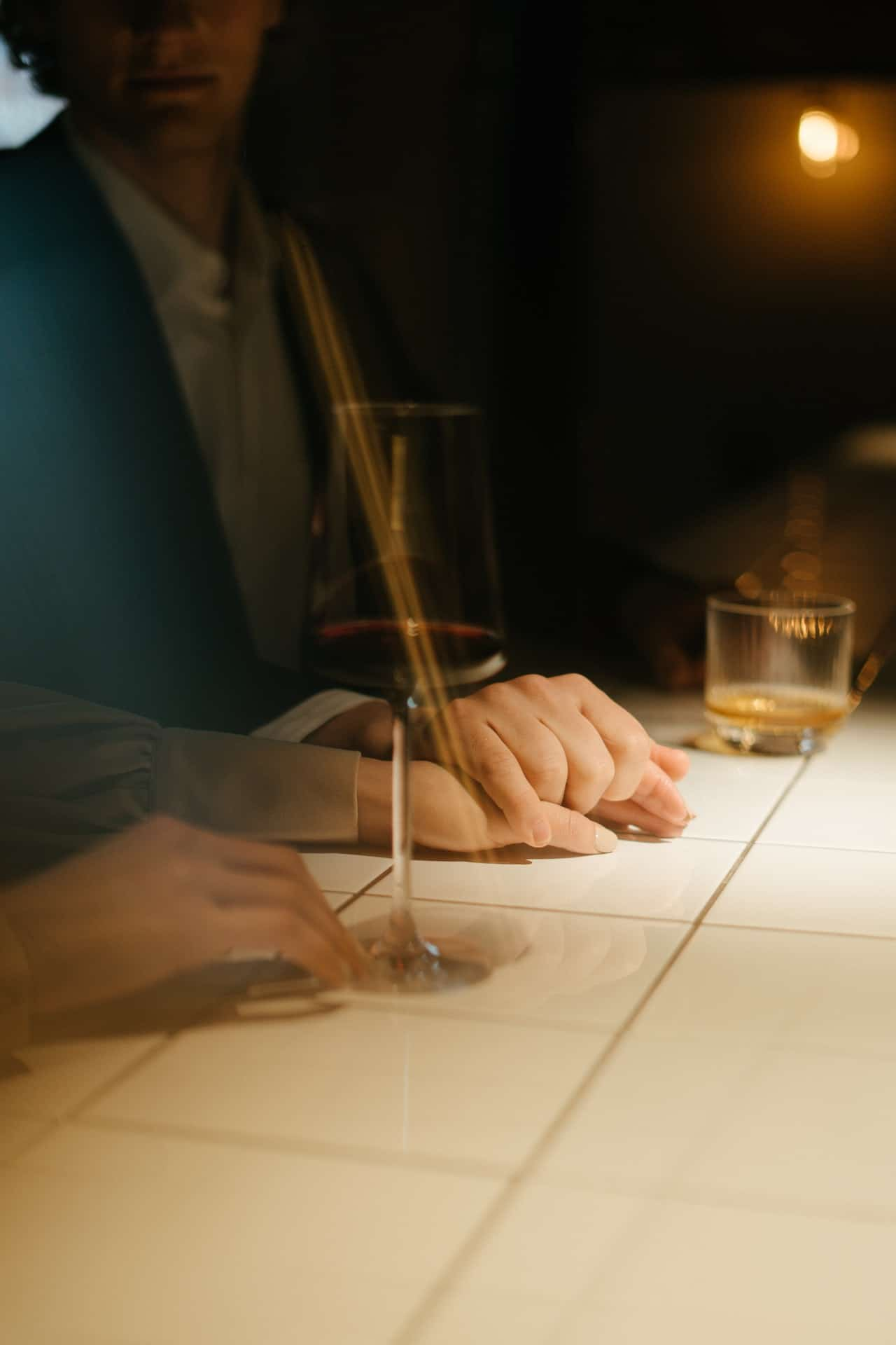 cropped man and woman sitting at the bar gently holding hands and having a drink