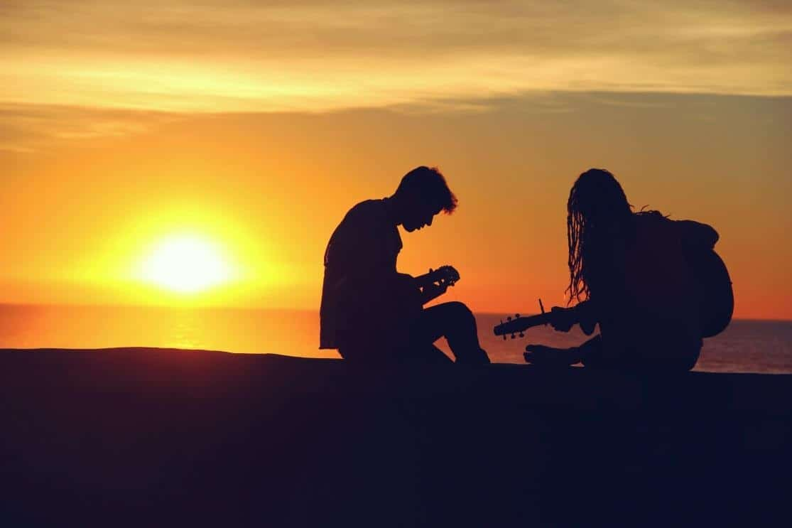 silhouette of couple playing music and having fun during sunset at the beach