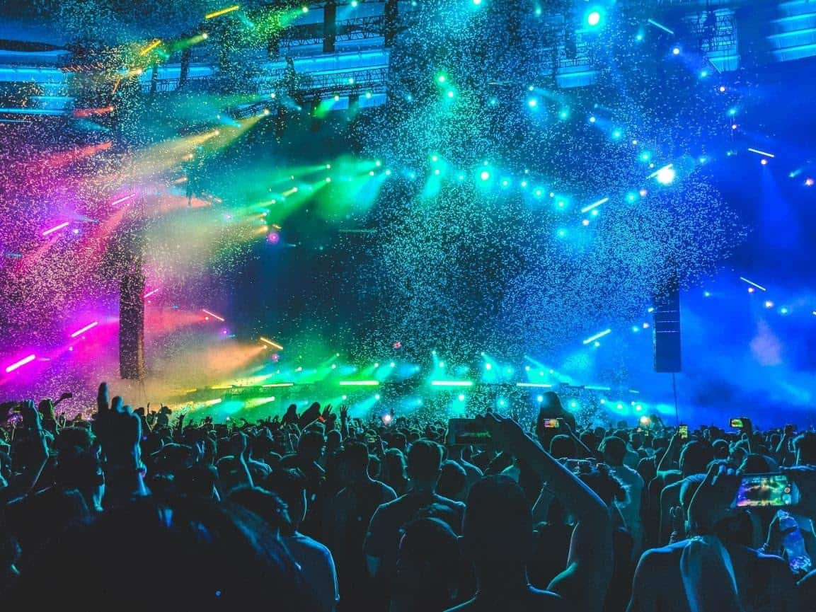 music festival stage with shiny lights, confetti and a dancing crowd