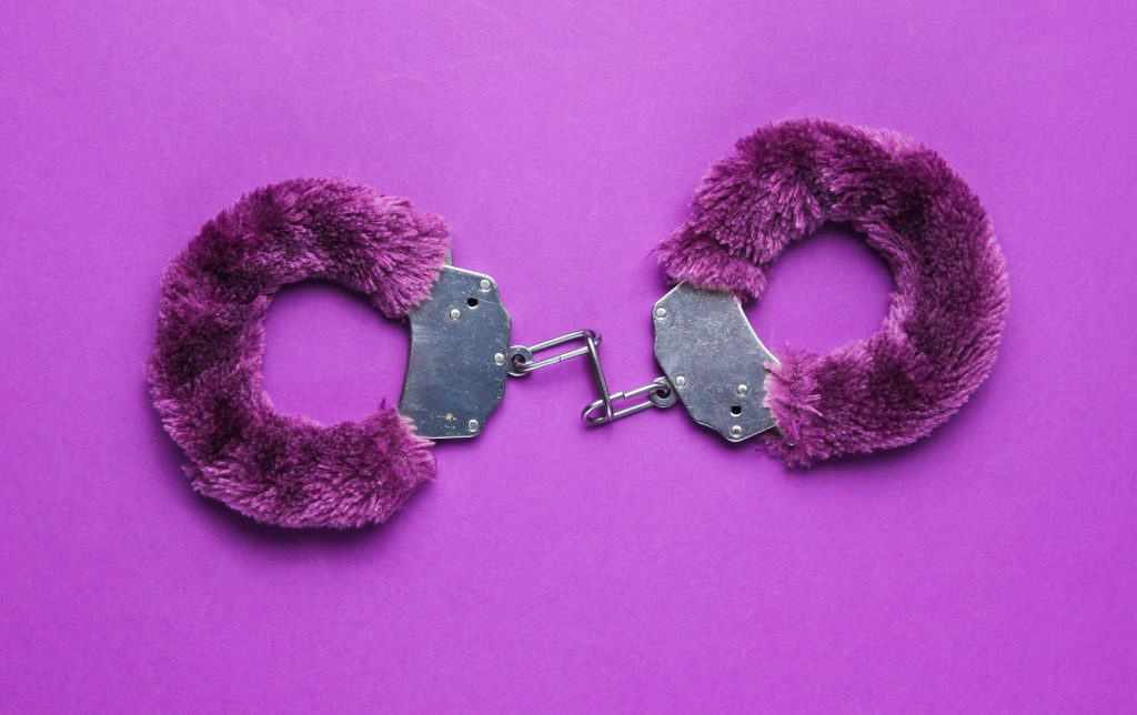 Handcuffs for sex games on purple background. Sexual bdsm toy.