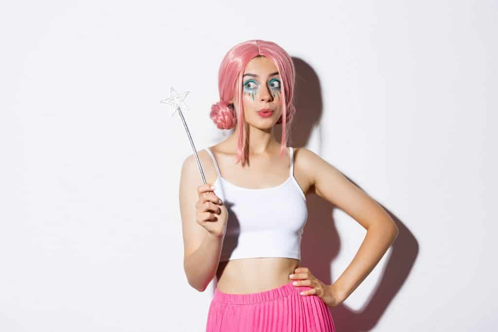 woman with pink wig and bright makeup, holding magic wand, cosplay fairy for halloween party, standing over white background