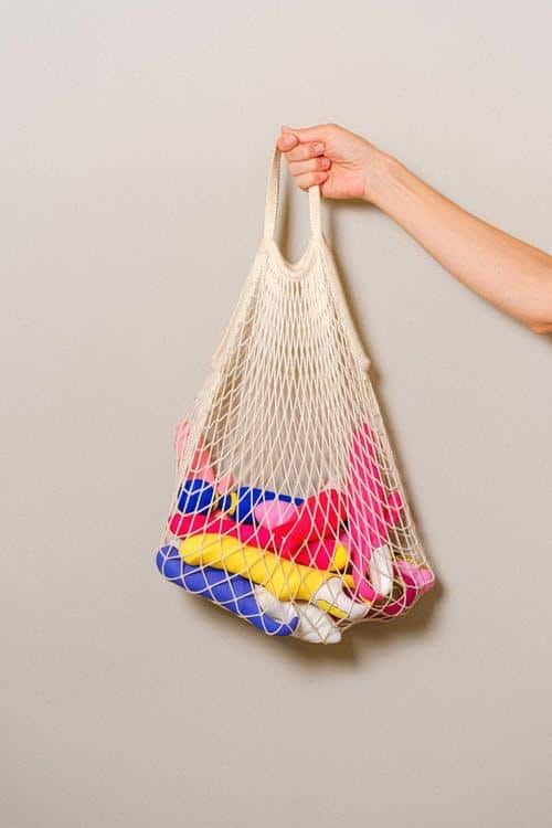 a hand holding a mesh bag with assorted dildos and vibrators