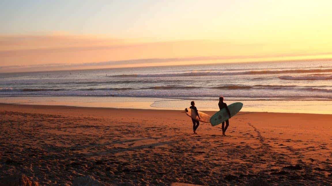 couple walking on the beach at sunset holding surfboards