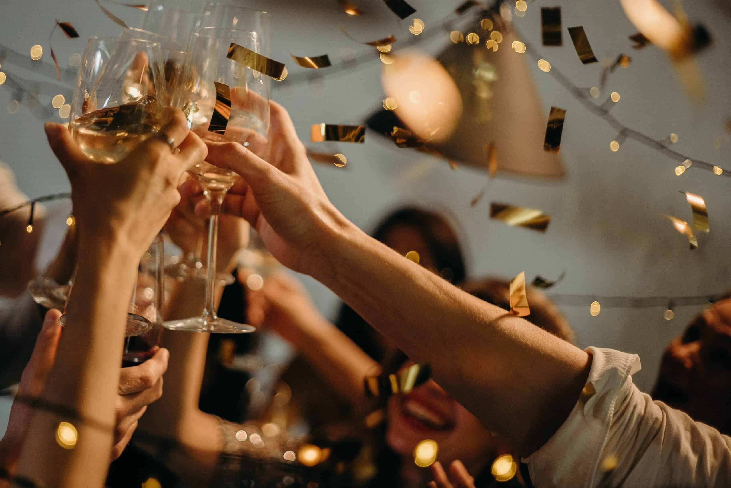 people cheering and clinking champagne glasses at office party