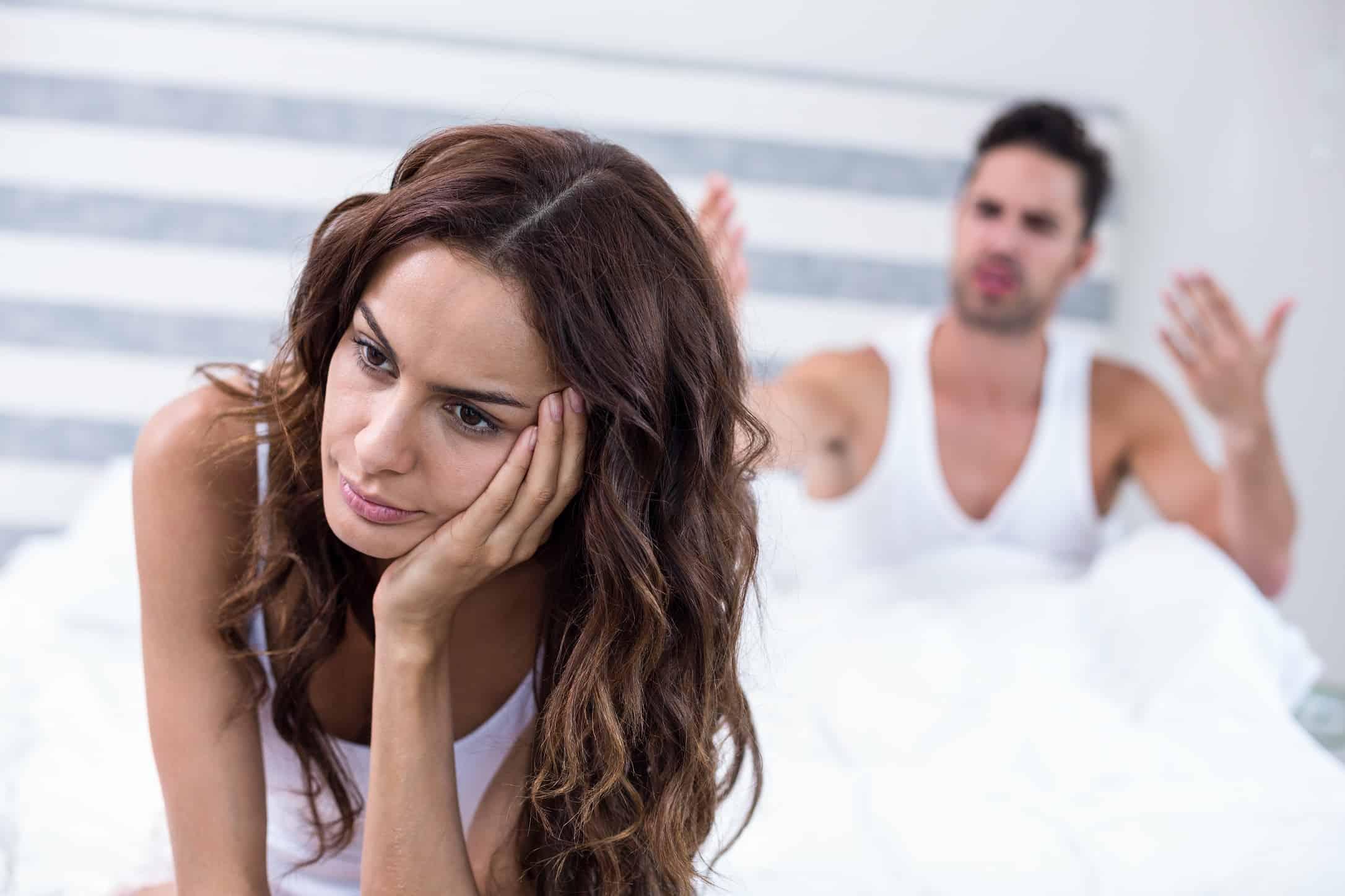 woman sad sit on bed man angry