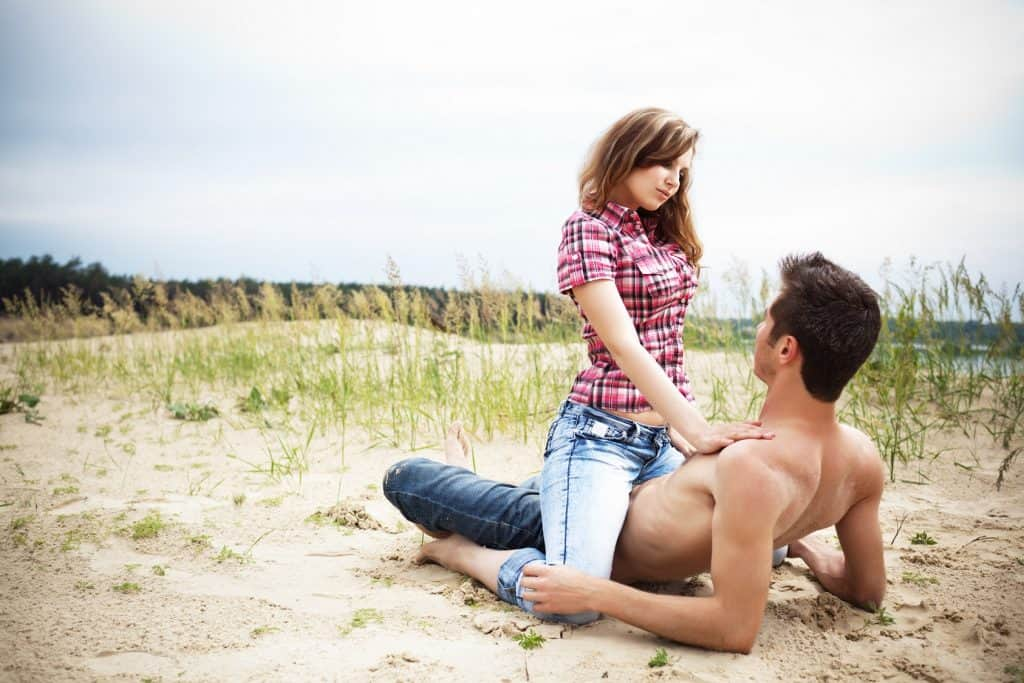 Young woman in jeans sitting on her boyfriend man on sandy ground on summer day with green nature at background