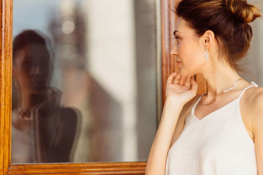 Attractive woman looking her reflection in the window