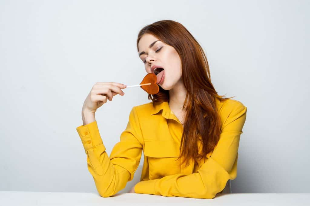 Woman lick lollipop in yellow sweatshirt