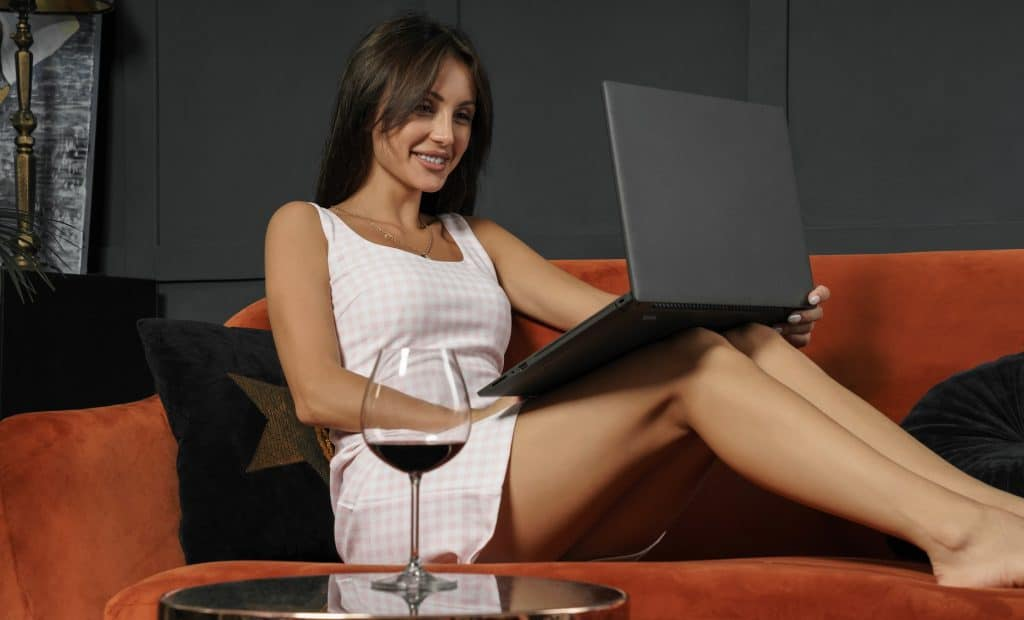 woman video chatting and drinking wine at home on the sofa