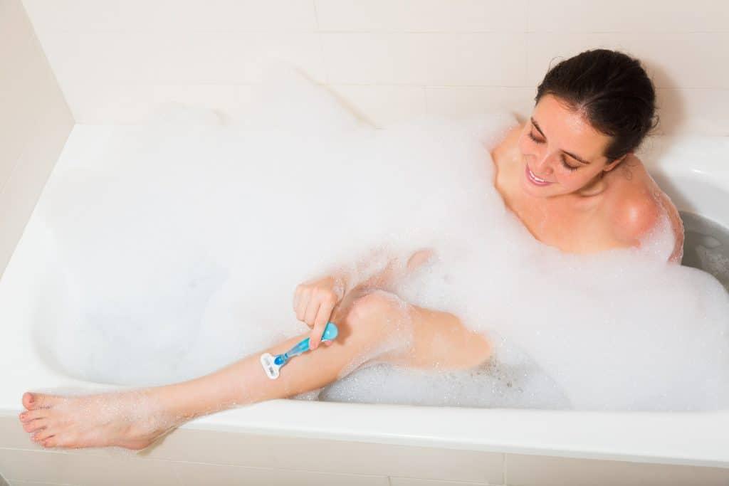 Woman shave legs in foam bath