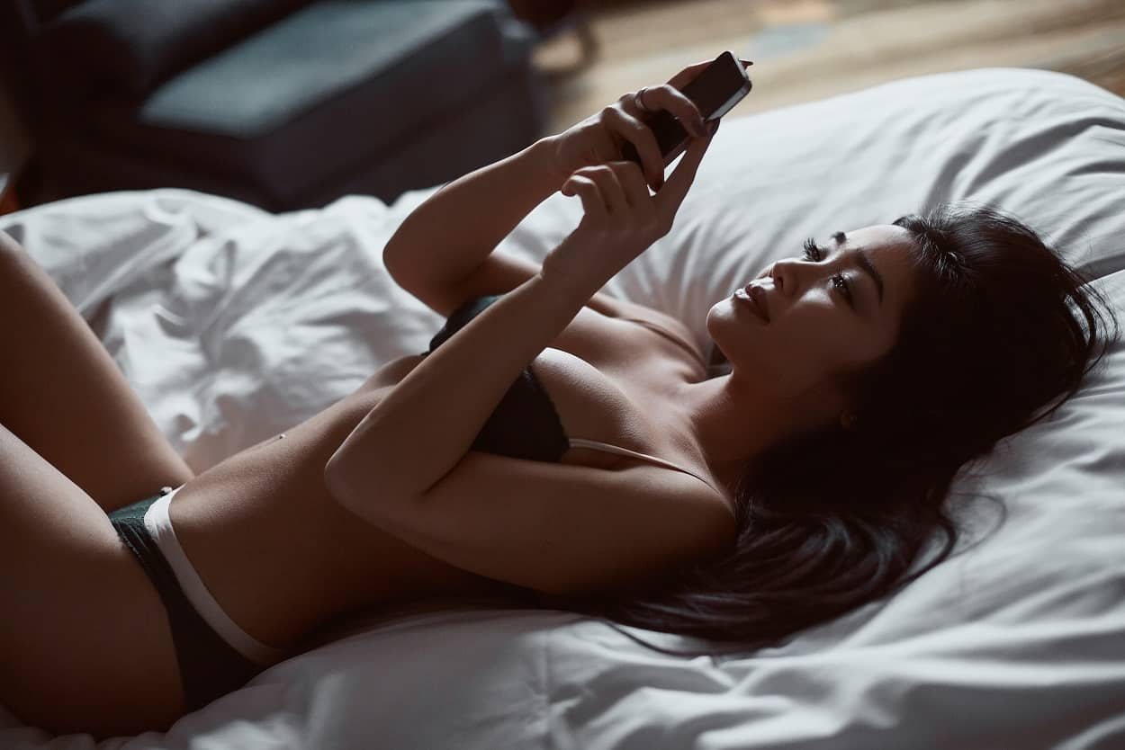 sensual woman in underwear lying on the bed holding her phone