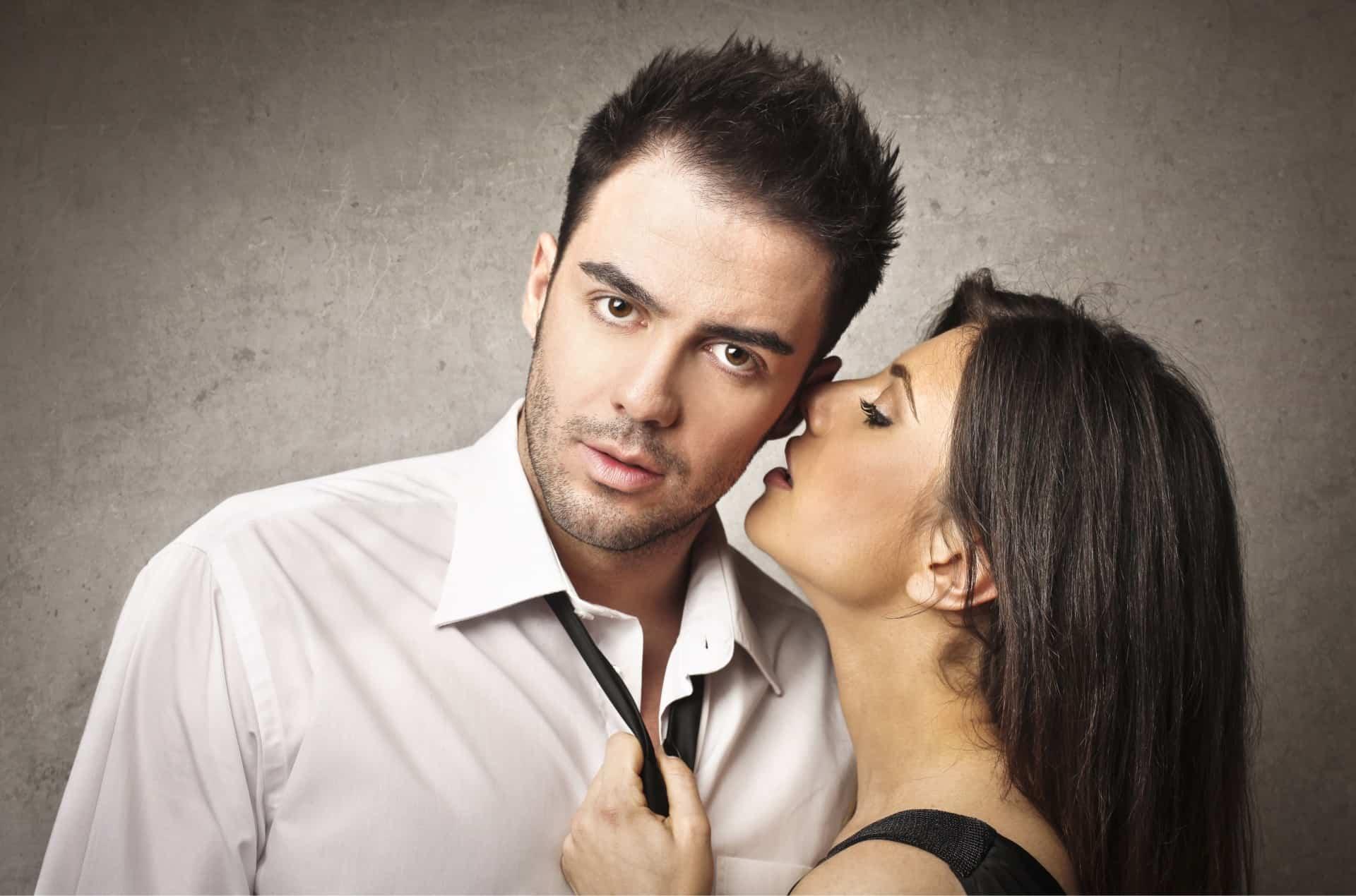 woman whisper a secret in a mans ear