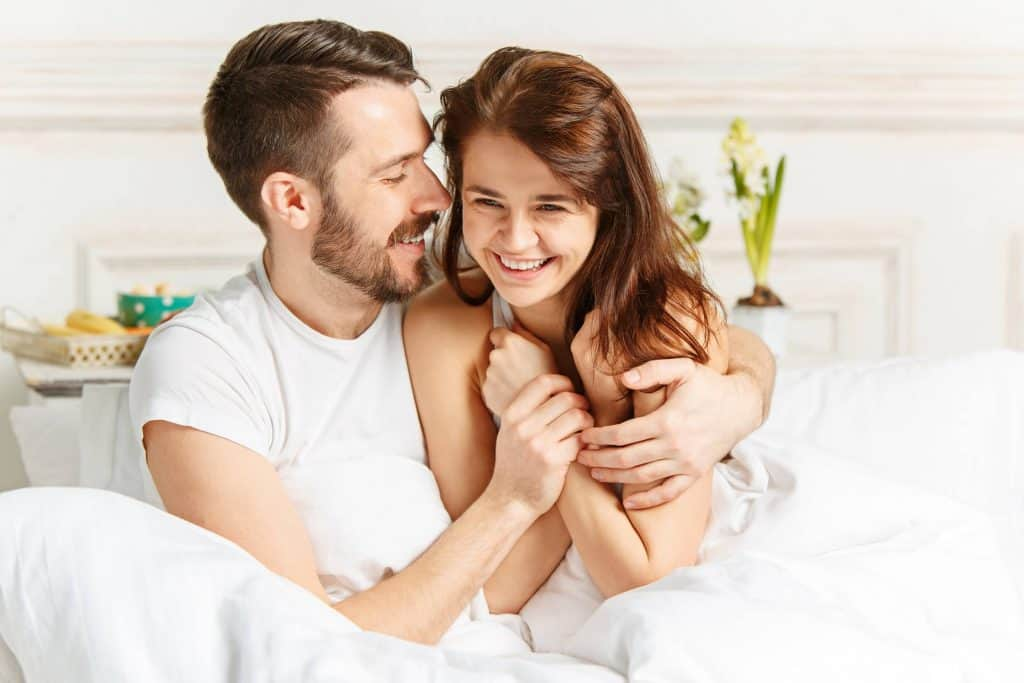 couple happy together in bed at home